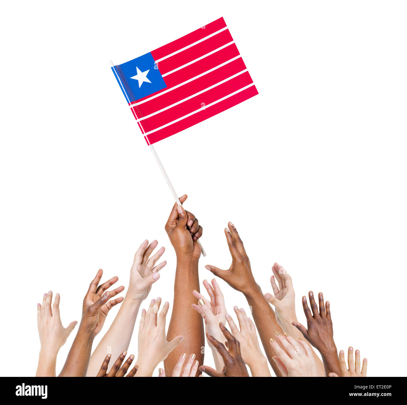 Group of multi-ethnic people reaching for and holding the flag of Liberia. - Stock Image