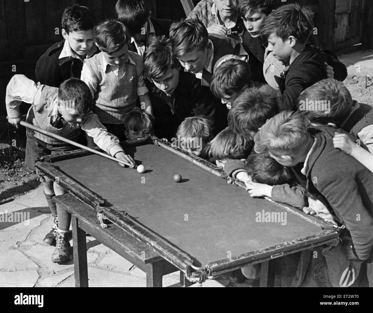 Sixteen tousled heads bend over a rickety billiard table at the Camel club, Bethnal Green, as 11 year old Ronnie - Stock Image