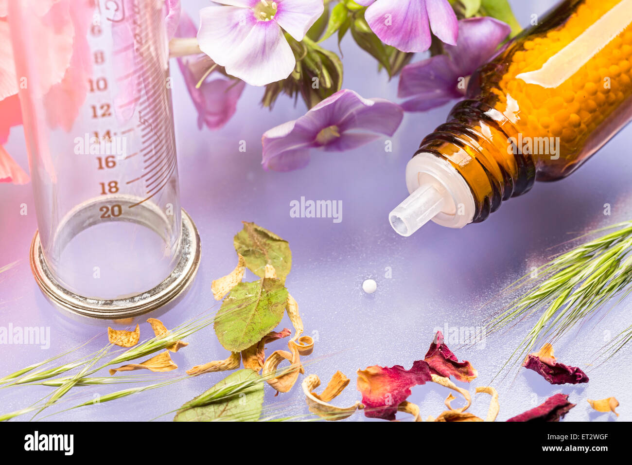 bottle with homeopathy globules, syringe and flowers - Stock Image