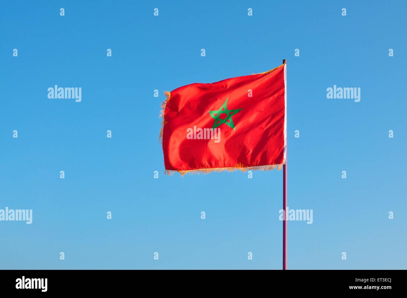 morocco national symbol pole flag waving over blue sky - Stock Image