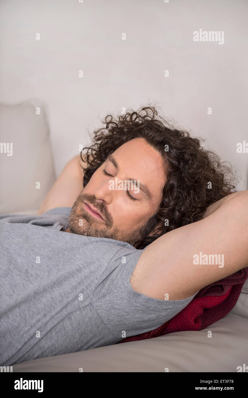 Mid adult man sleeping on couch, Munich, Bavaria, Germany - Stock Image
