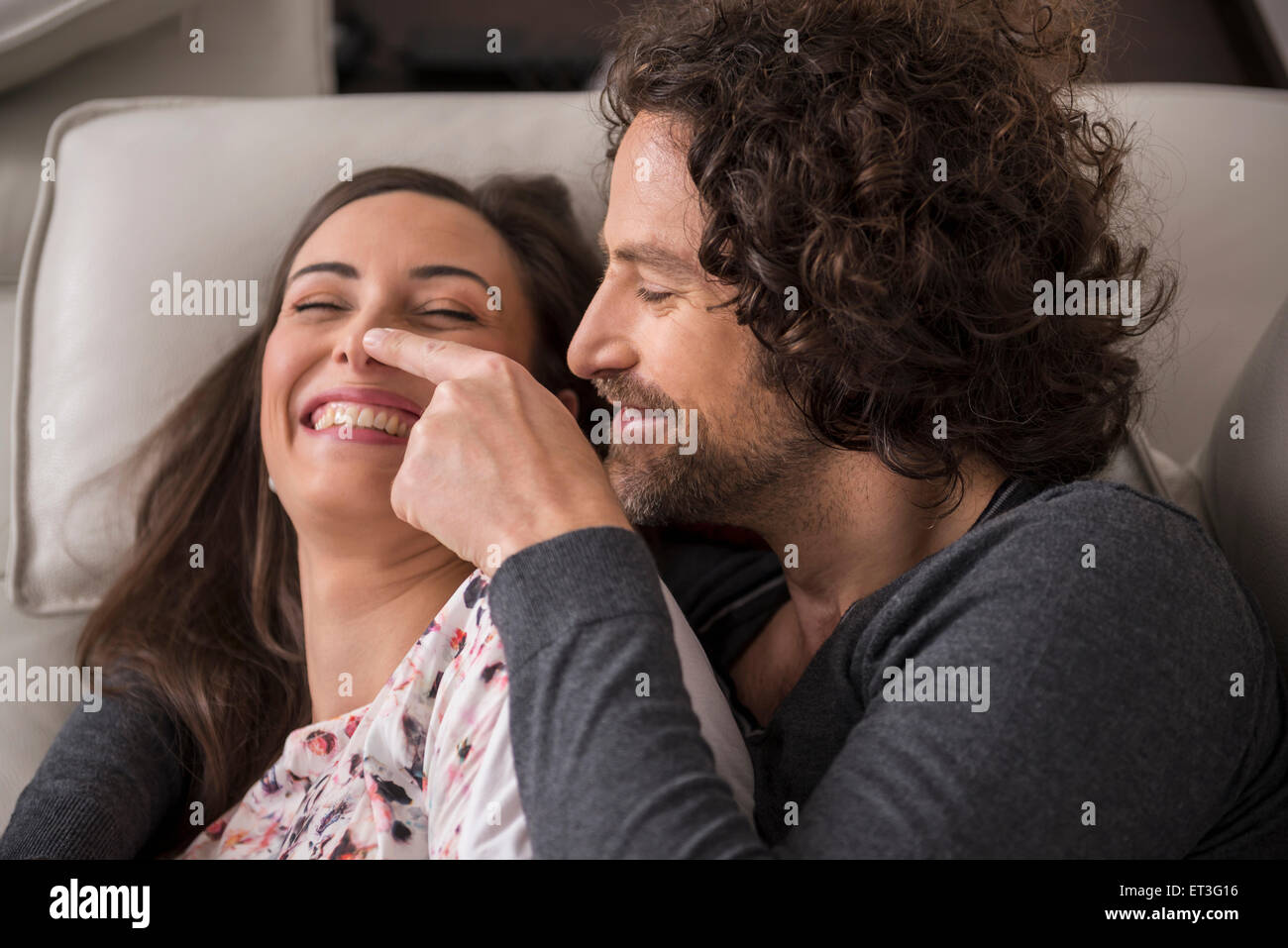 Mid adult couple lying on sofa and smiling, Munich, Bavaria, Germany - Stock Image