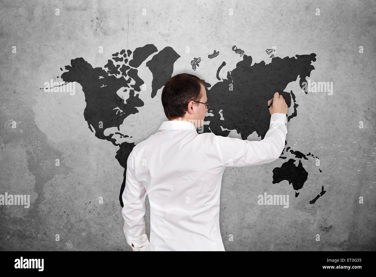 Young businessman drawing world map on concrete wall stock photo young businessman drawing world map on concrete wall gumiabroncs Gallery