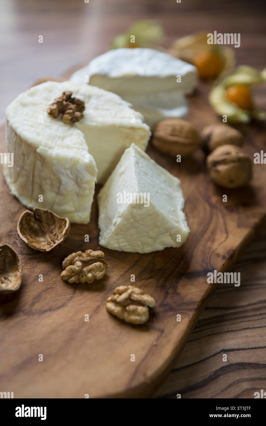 Close-up of cheese and walnuts on chopping board, Germany Stock Photo