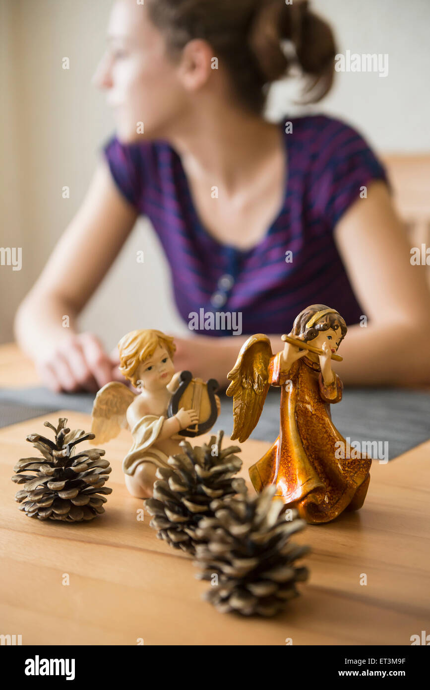 Decorative Christmas angel figurines with musical instruments and pine cones in front of teenage girl, Bavaria, - Stock Image