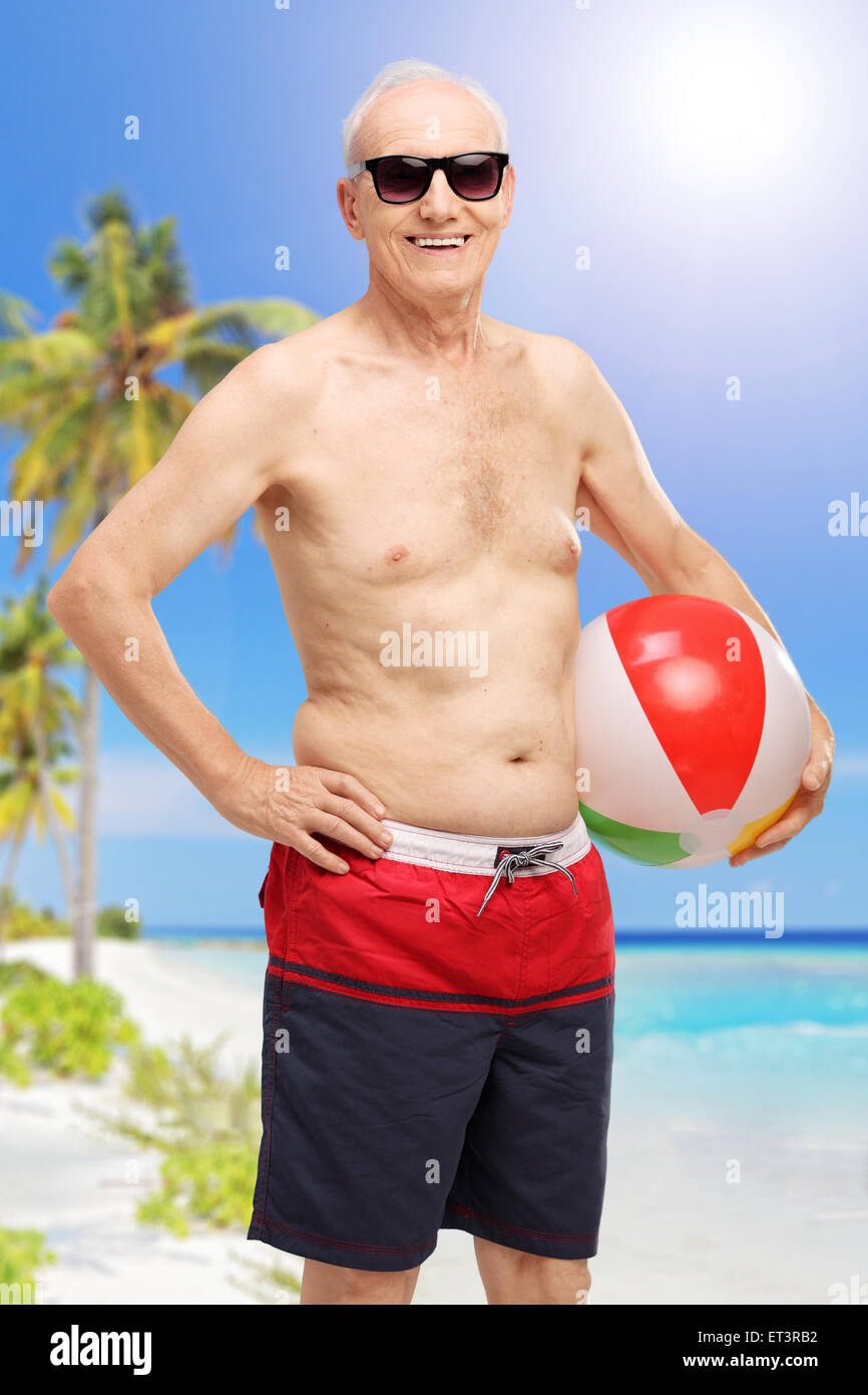 Vertical shot of a senior in swim shorts holding a beach ball at a beach and looking at the camera - Stock Image