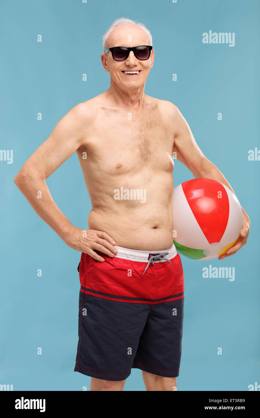 Vertical shot of a shirtless senior in swim shorts holding a beach ball and looking at the camera on blue background - Stock Image