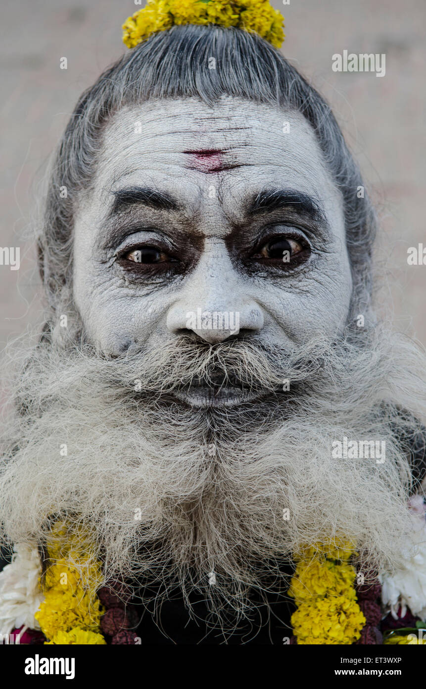 A sadhu poses for a photograph on the banks of the Ganges - Stock Image