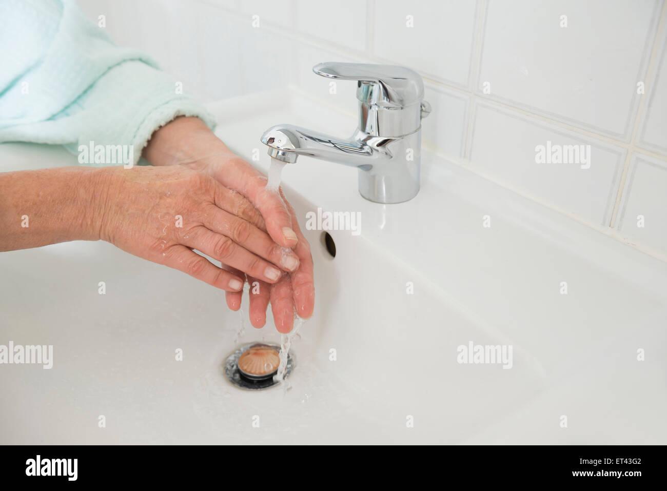 Senior woman washing hands in bathroom sink, Munich, Bavaria, Germany - Stock Image