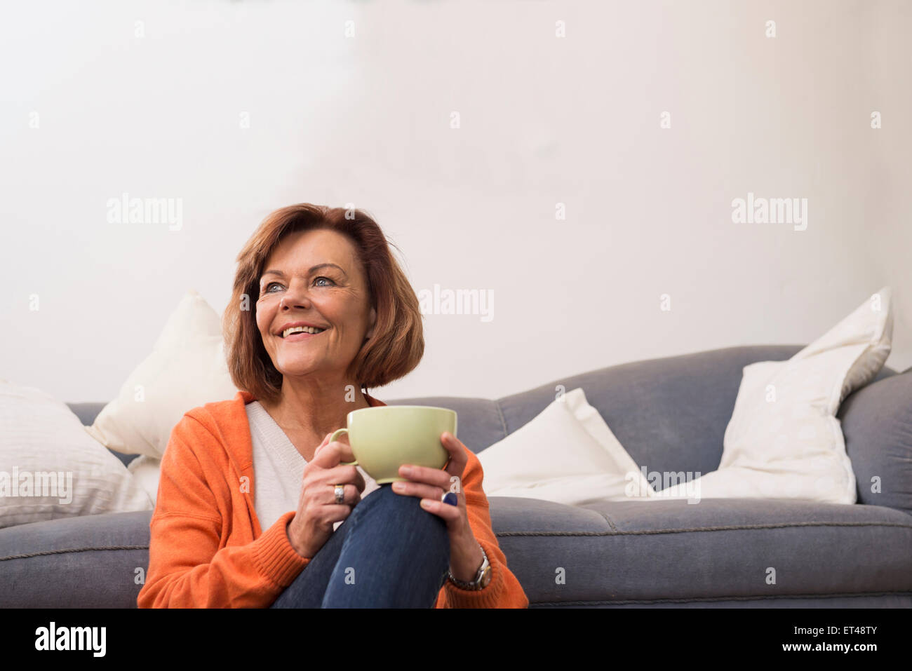 Senior woman dreaming while drinking tea at home, Munich, Bavaria, Germany - Stock Image
