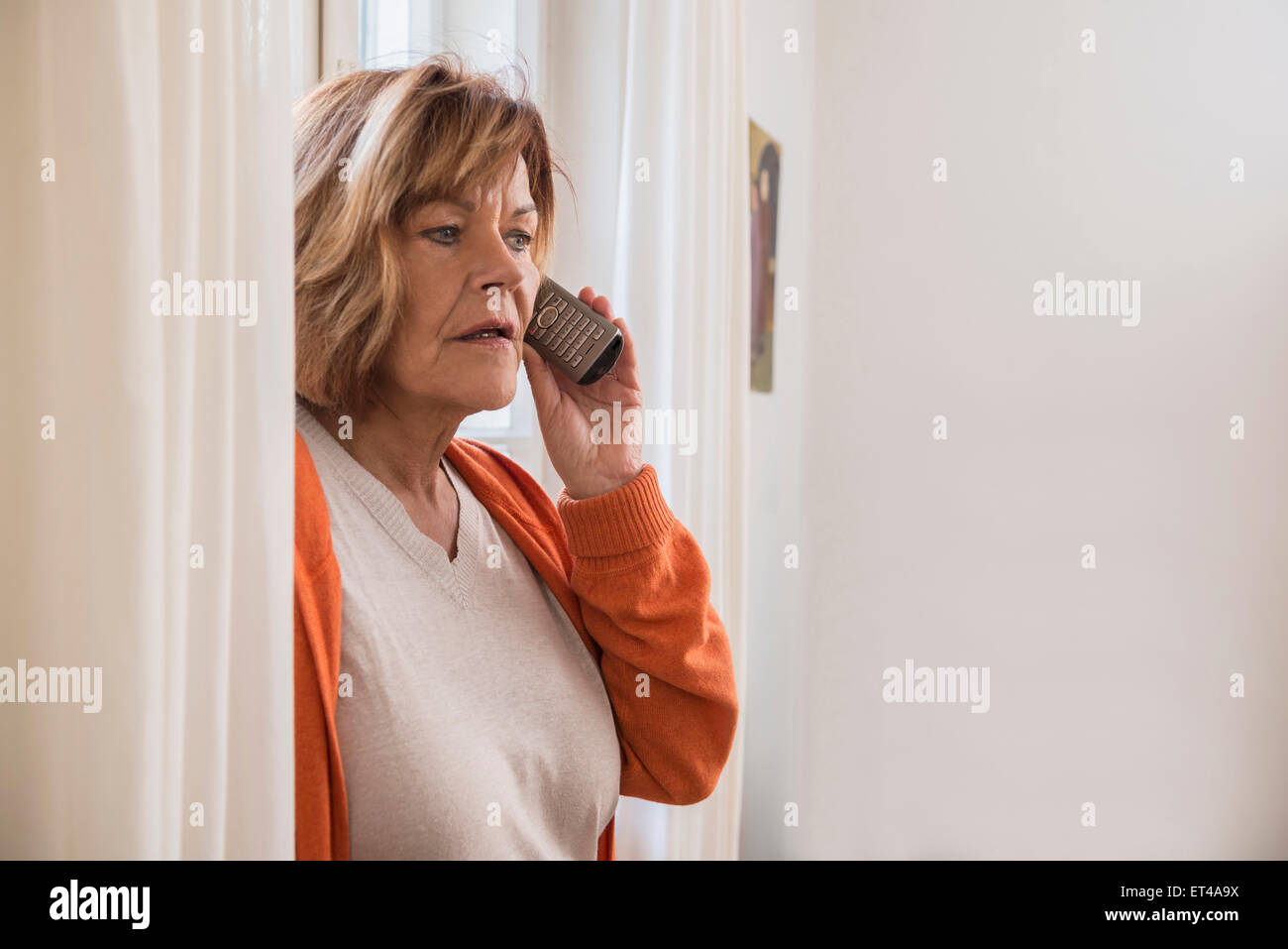 Senior woman talking on a mobile phone looking shocked, Munich, Bavaria, Germany - Stock Image
