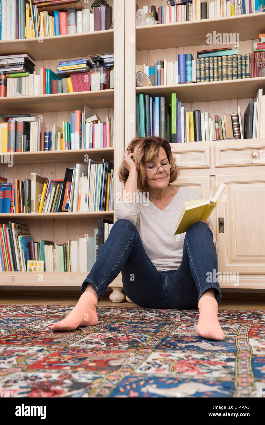 Senior woman sitting on the floor in front of bookshelf and reading, Munich, Bavaria, Germany - Stock Image