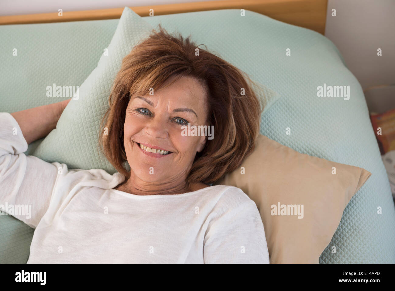 Portrait of senior woman lying on bed and smiling, Munich, Bavaria, Germany - Stock Image