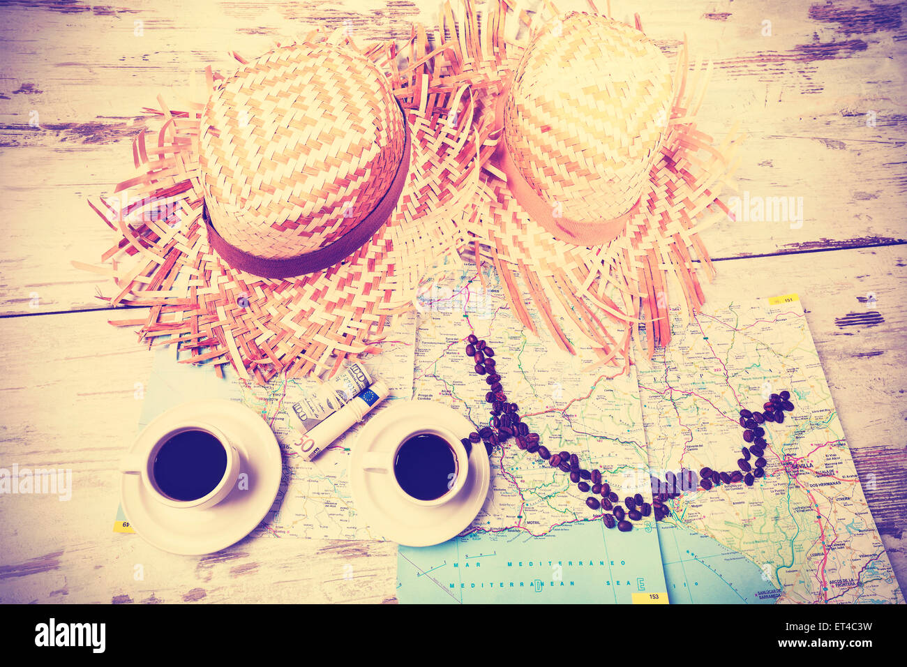 Vintage instagram stylized summer adventure concept with coffees, map, money and hats on wooden table. - Stock Image