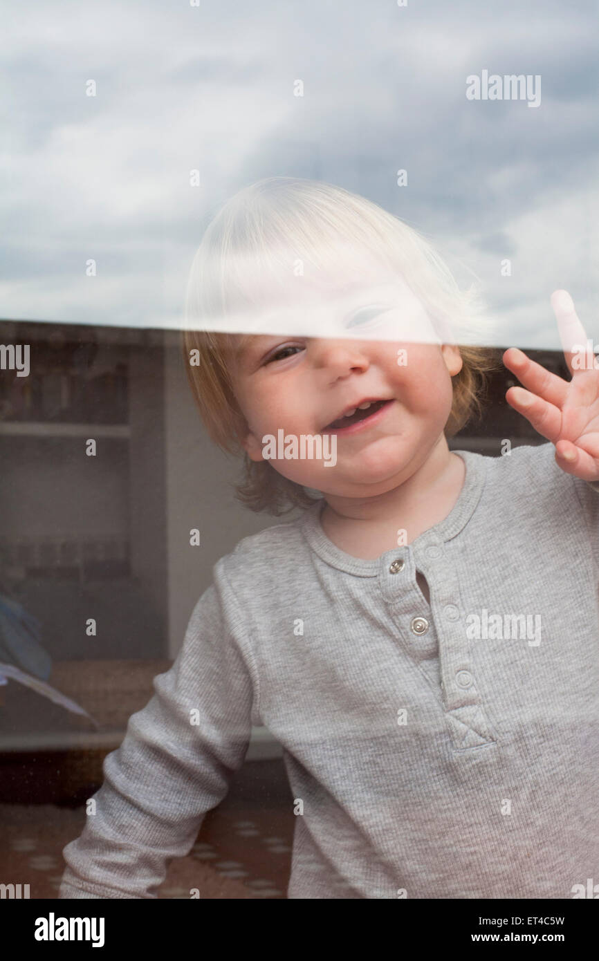 portrait of smiling blonde caucasian baby nineteen month age chubby face looking at camera through reflecting glass Stock Photo