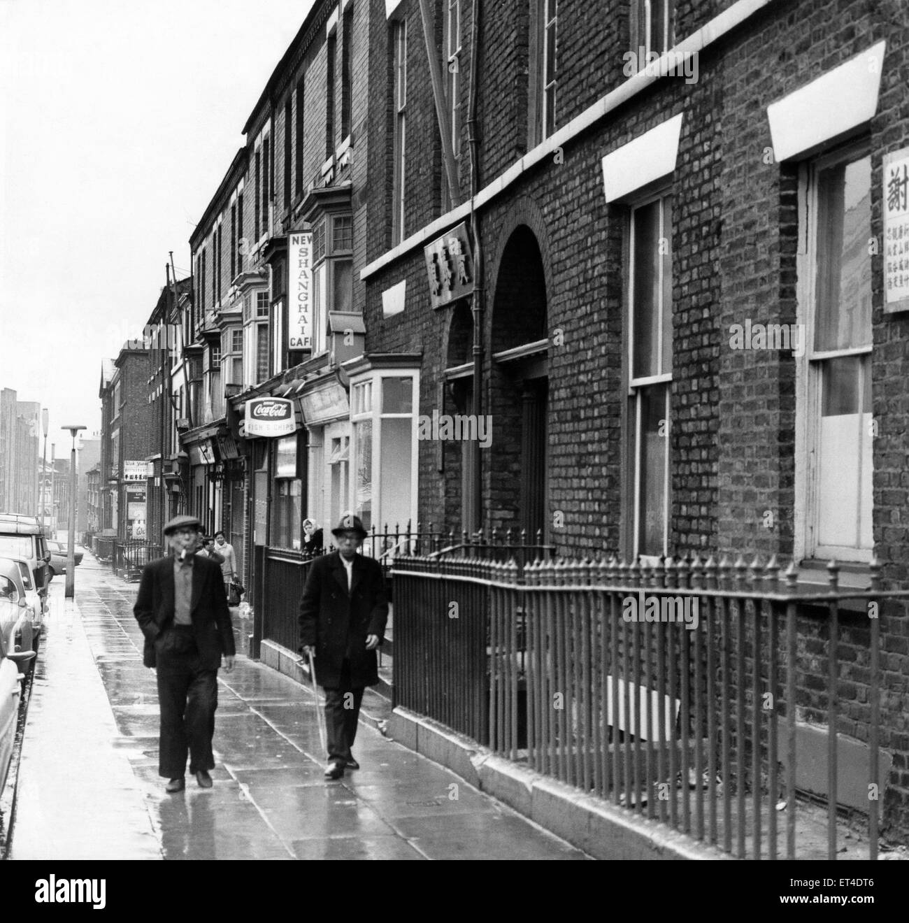 Two chinese men walking down Nelson Street in Chinatown, Liverpool, Merseyside. Circa 1968. - Stock Image