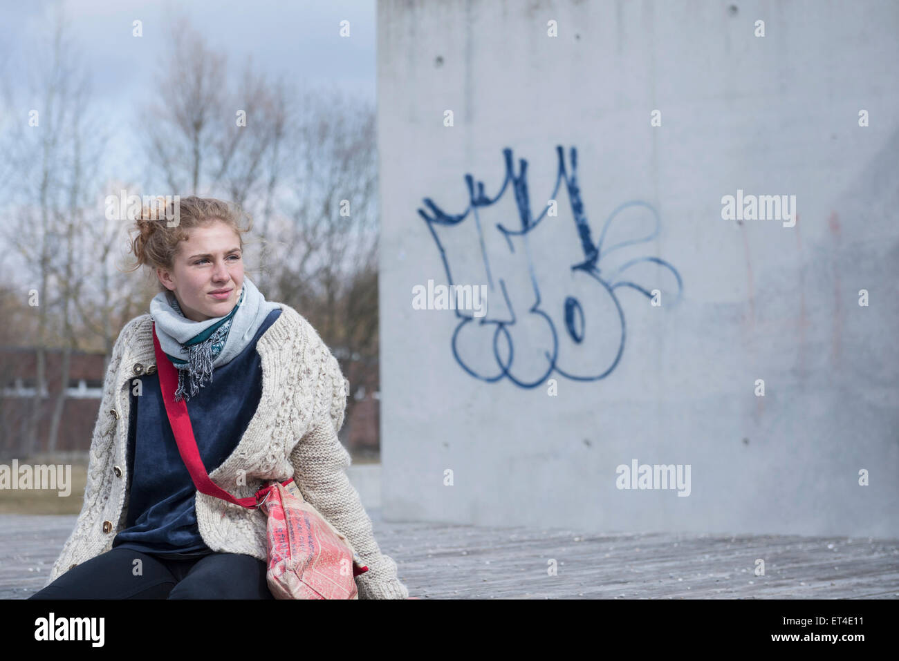 Young woman sitting on bench and waiting Munich Bavaria Germany - Stock Image