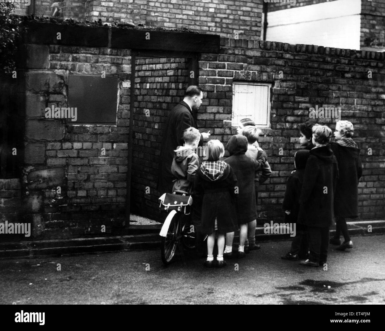 Detective-Sergeant L. Alton of Scotland Yard, talks to children outside the back door of the house where Katherine - Stock Image