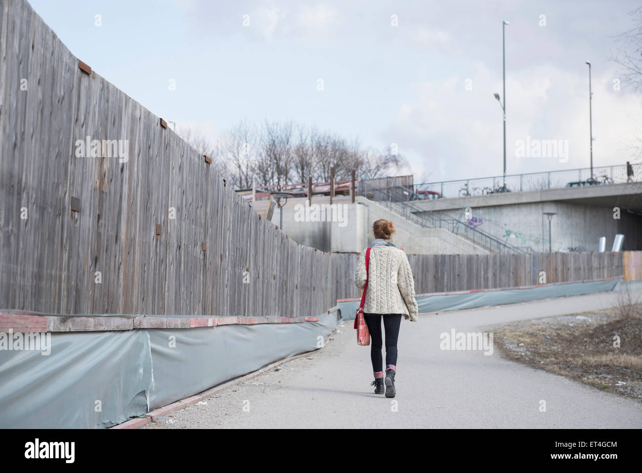 Rear view of a young woman walking along construction site fence on road Munich Bavaria Germany - Stock Image