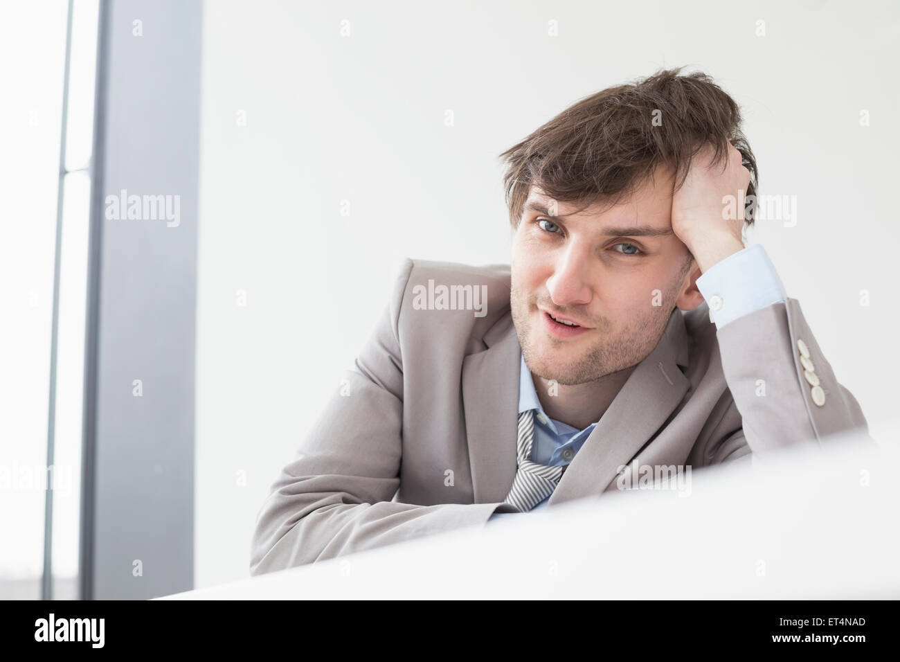 Businessman leaning on desk in office, Leipzig, Saxony, Germany - Stock Image