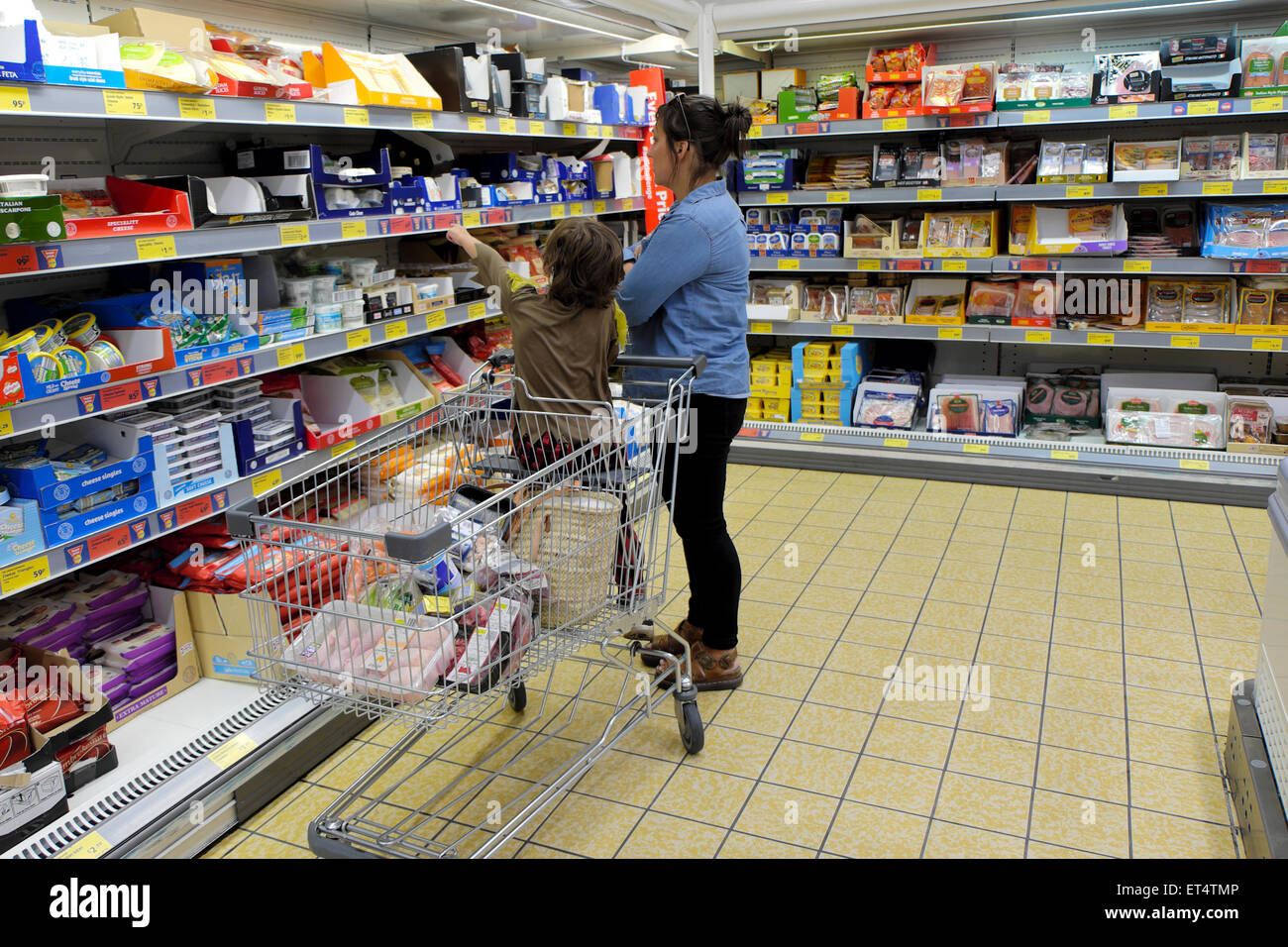 Mother and child shopping for dairy products in Aldi supermarket on the  cheese and yogurt refrigeration aisle in - Stock Image