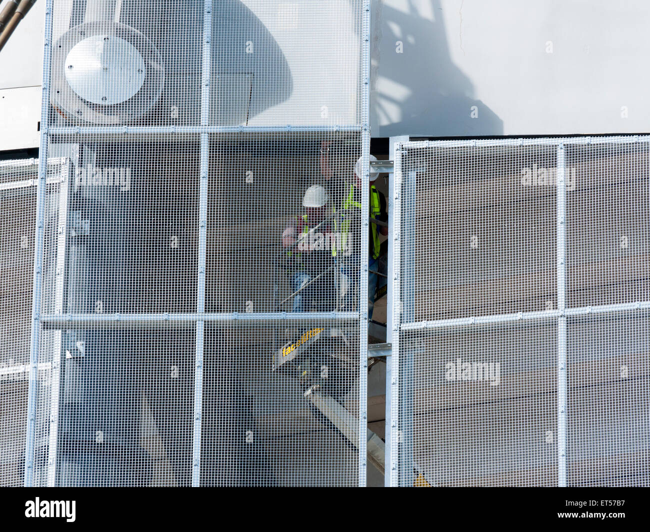 Workmen on an access platform installing mesh panels, South Stand expansion works, Etihad Stadium, Manchester, England, - Stock Image