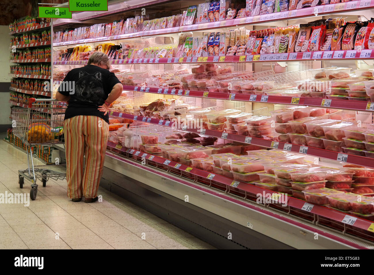 GERMANY - MAY 2015: Customer selecting packaged meat in refrigerated section of a Kaufland hypermarket - Stock Image