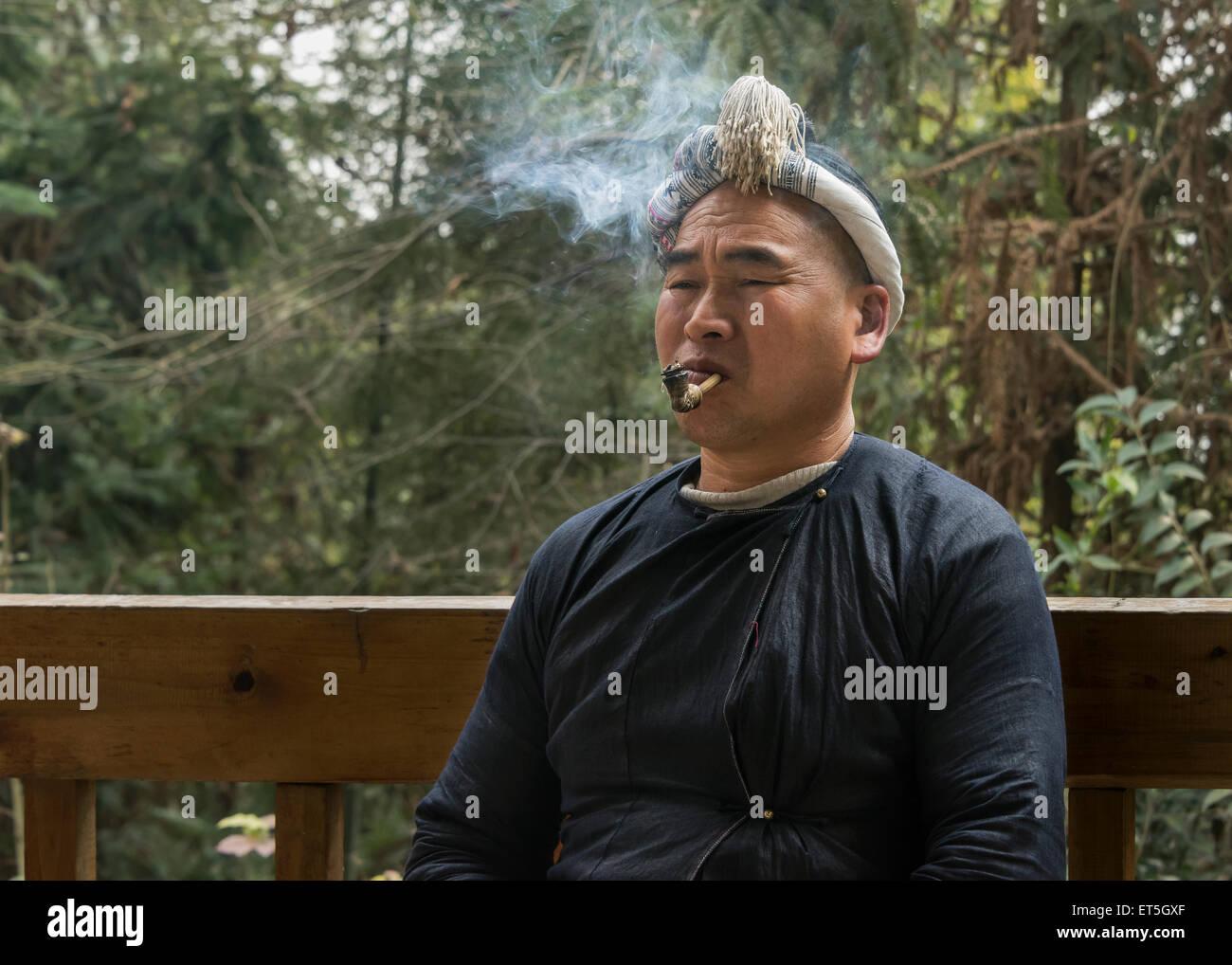 Basha Miao man smoking a pipe, Basha Gun Village, Guizhou Province, China - Stock Image