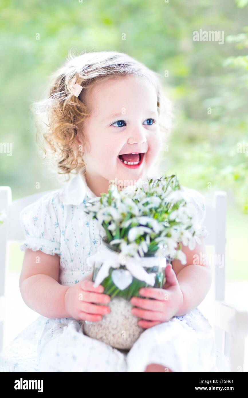 Beautiful curly toddler girl in a white dress sitting in a white rocking chair holding first spring flowers in crystal - Stock Image