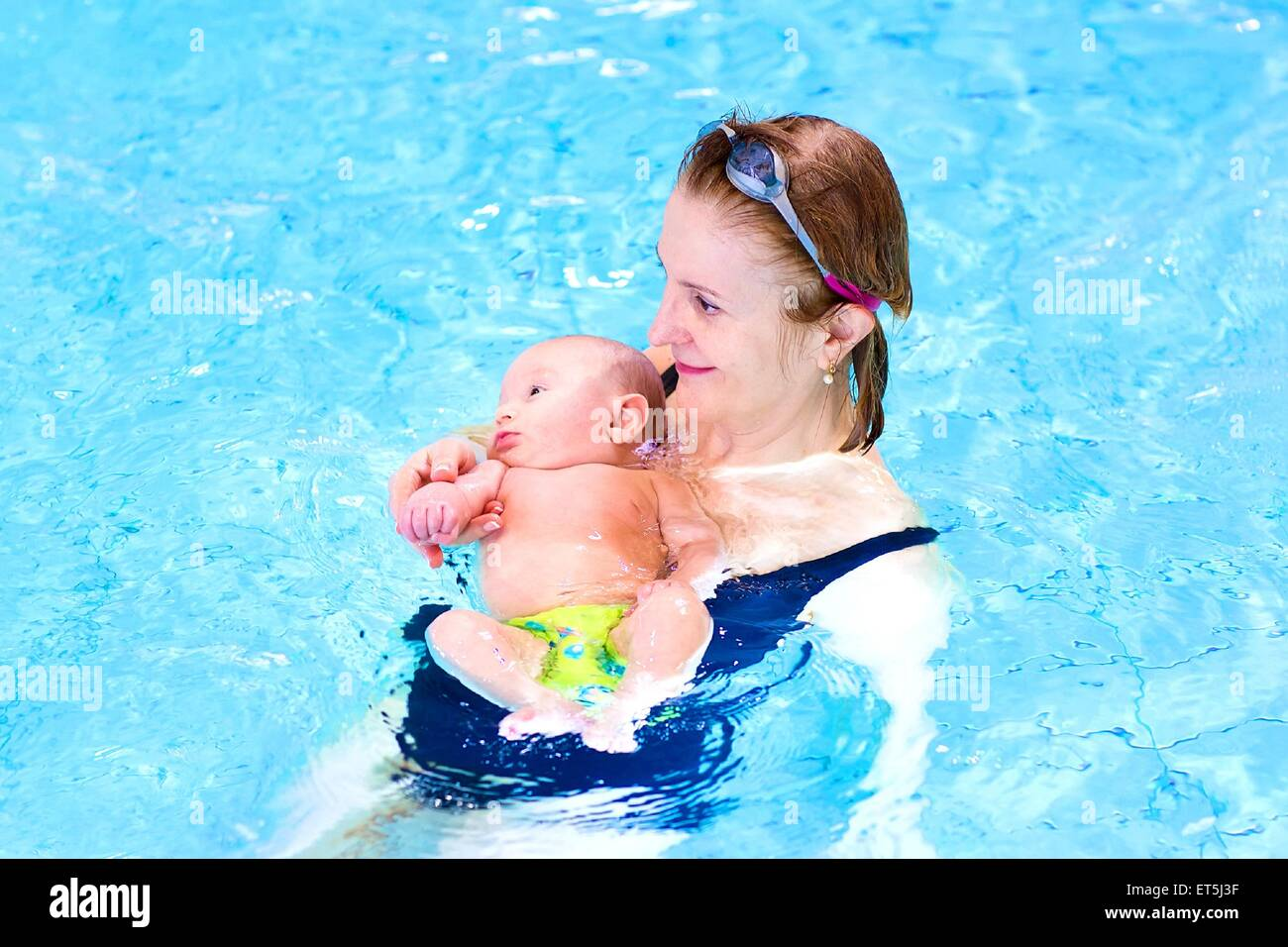 Attractive woman and a cute baby boy relaxing in a swimming pool - Stock Image