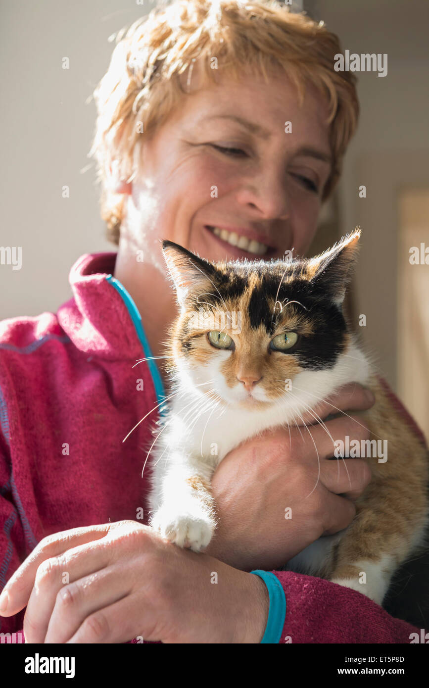 Close-up of mature woman with cat in her arms, Bavaria, Germany - Stock Image