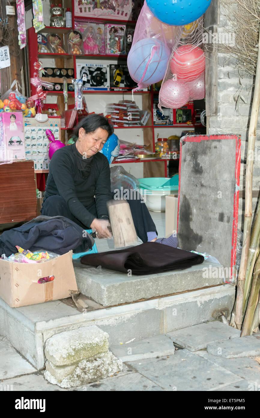 Woman vigorously pounding cloth to make it shiny, Zhaoxing Dong Village, Guizhou Province, China - Stock Image