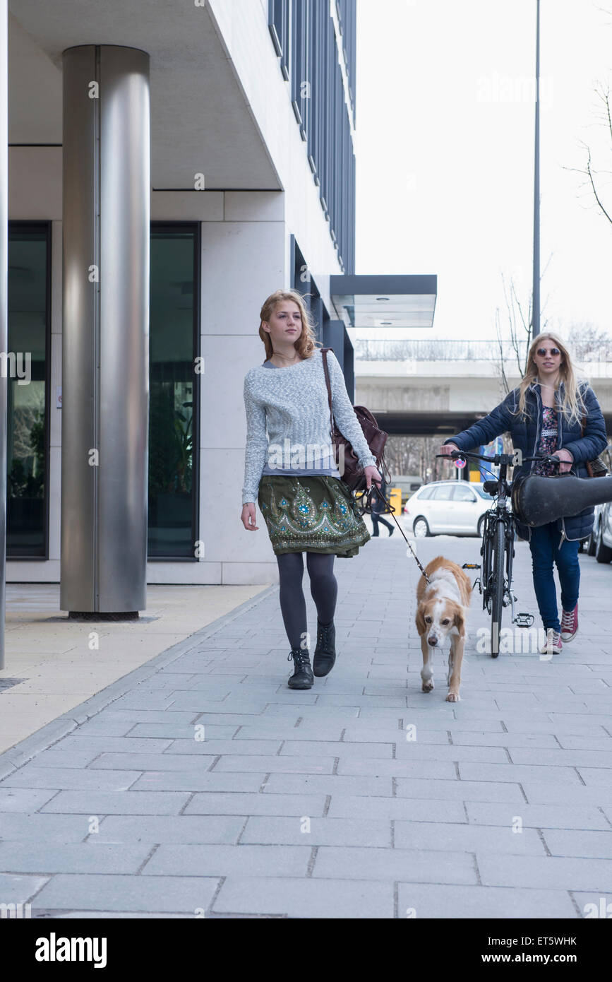 Women walking with her dog beside teenage girl, Munich, Bavaria, Germany - Stock Image