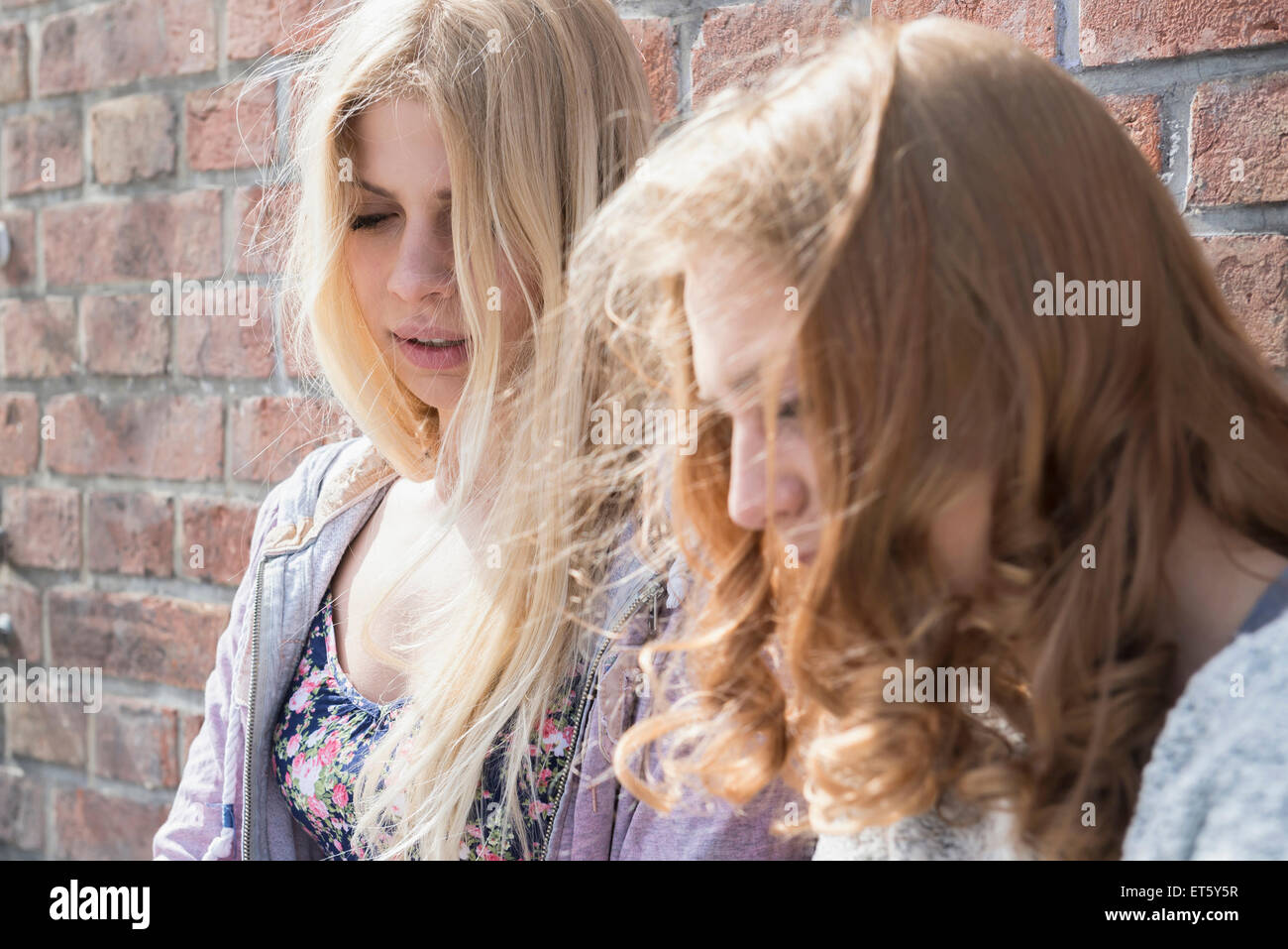 Two women leaning in front of brick wall, Munich, Bavaria, Germany - Stock Image