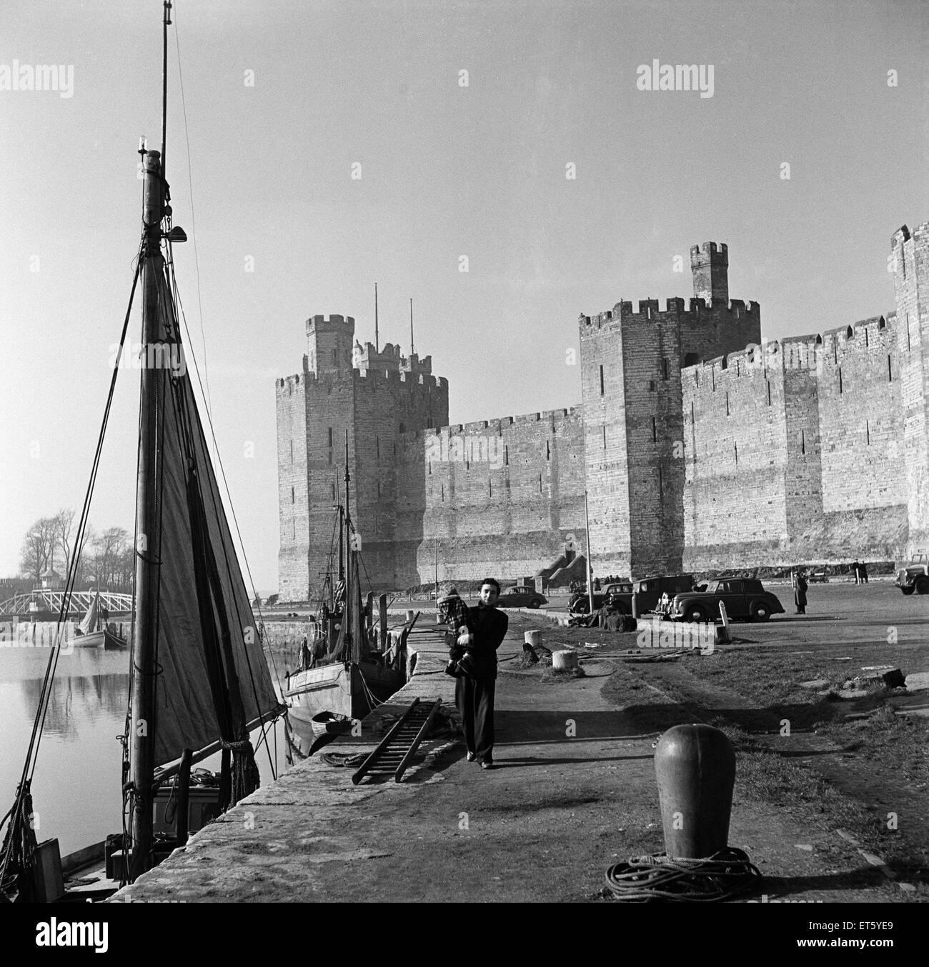 A man walking past Caernarfon Castle, Gwynedd. Circa 1952. - Stock Image