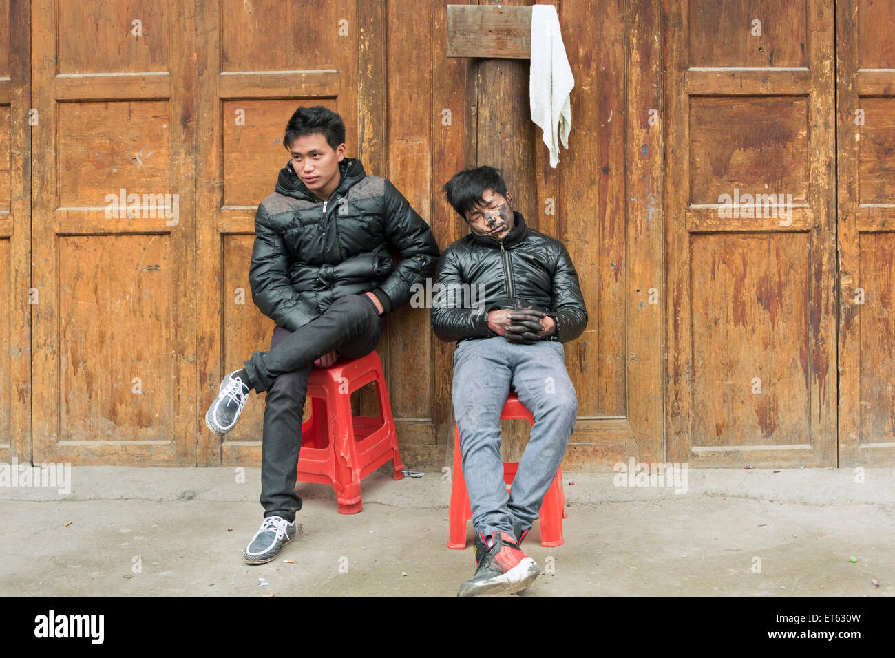Standing by his sleeping friend, Huanggang Dong Village, Guizhou Province, China - Stock Image