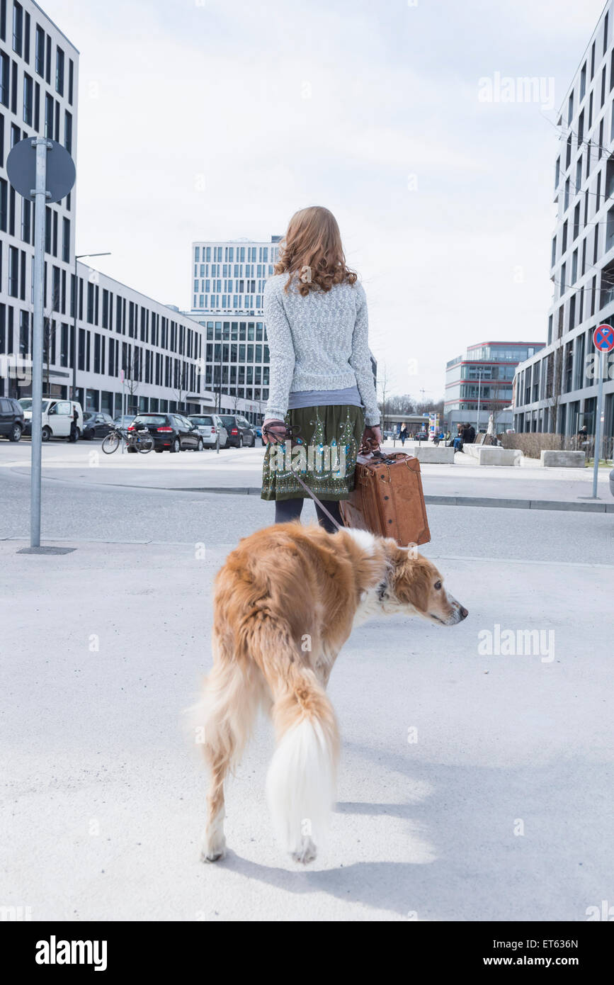 Rear view of woman walking on road with dog and suitcase, Munich, Bavaria, Germany - Stock Image
