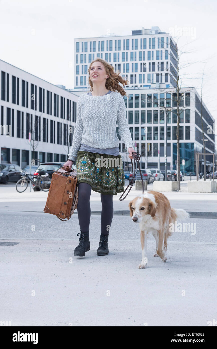 Young woman walking on road with dog and suitcase, Munich, Bavaria, Germany - Stock Image