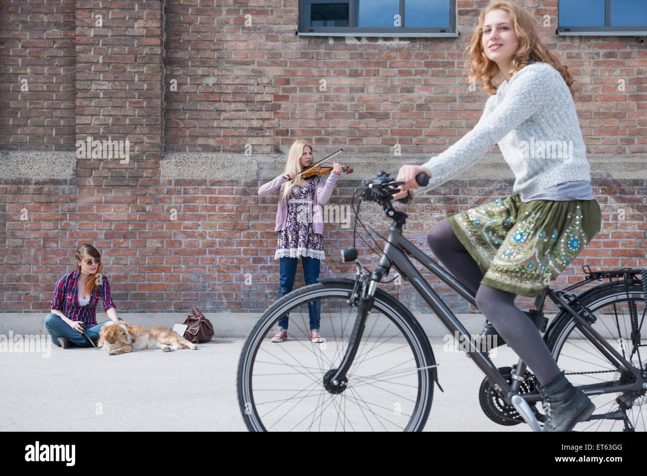 Woman riding bicycle on street with teenage girl playing violin in background, Munich, Bavaria, Germany Stock Photo