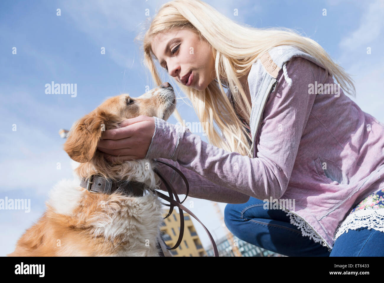Low angle view of teenage girl kissing her dog, Munich, Bavaria, Germany - Stock Image