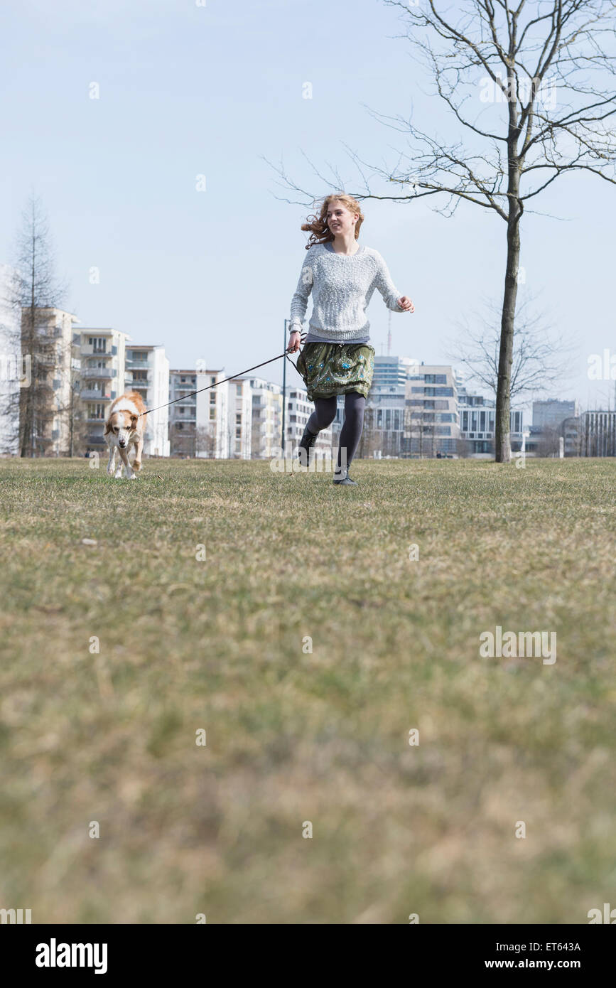 Young woman running in park with dog, Munich, Bavaria, Germany - Stock Image