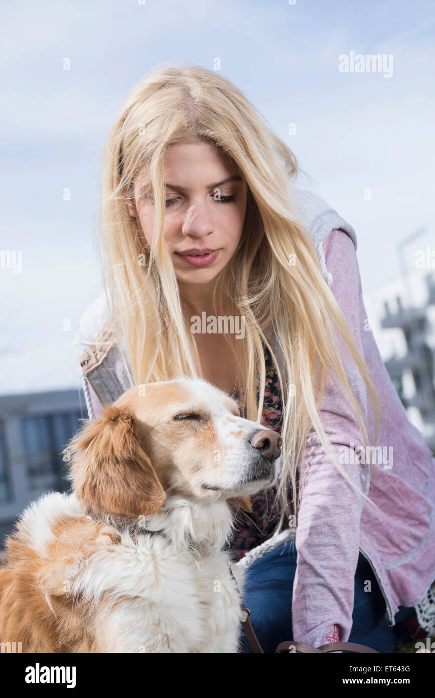 Low angle view of teenage girl looking at her dog, Munich, Bavaria, Germany - Stock Image