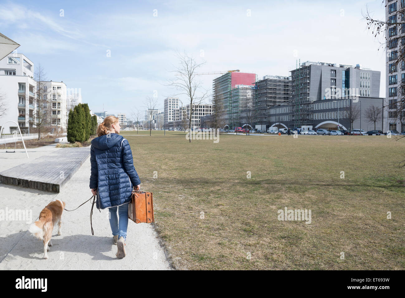 Rear view of woman walking on sidewalk with dog and suitcase, Munich, Bavaria, Germany - Stock Image