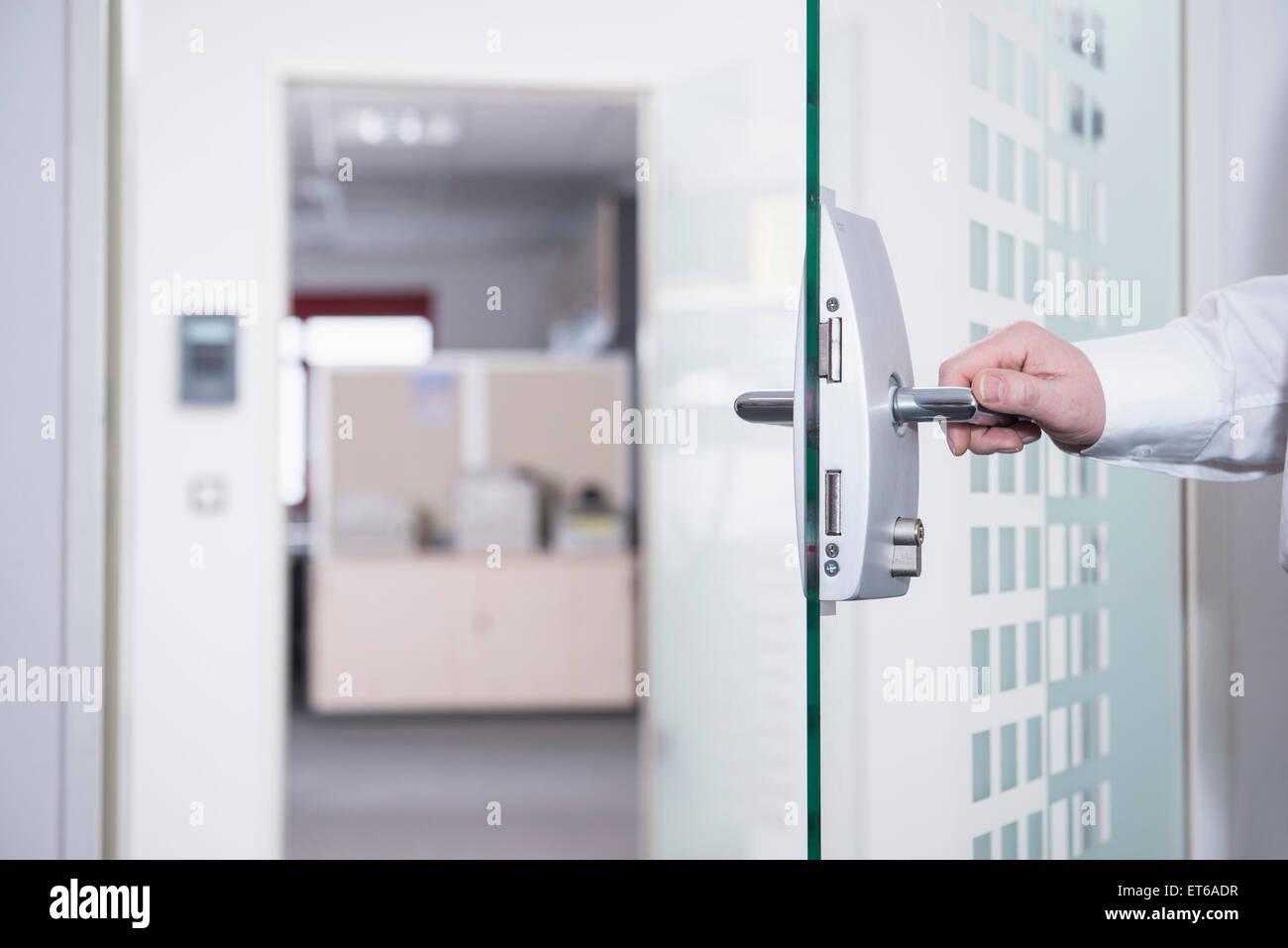 Businessman opening office door, Munich, Bavaria, Germany - Stock Image