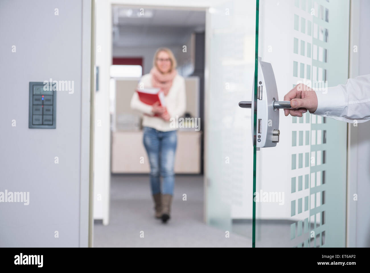 Businessman opening office door for his colleague, Munich, Bavaria, Germany - Stock Image
