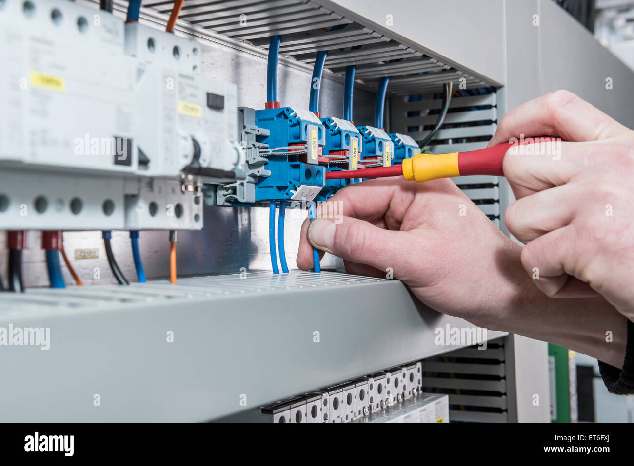 Close-up of electrician screwing cable in distribution fusebox, Munich, Bavaria, Germany - Stock Image