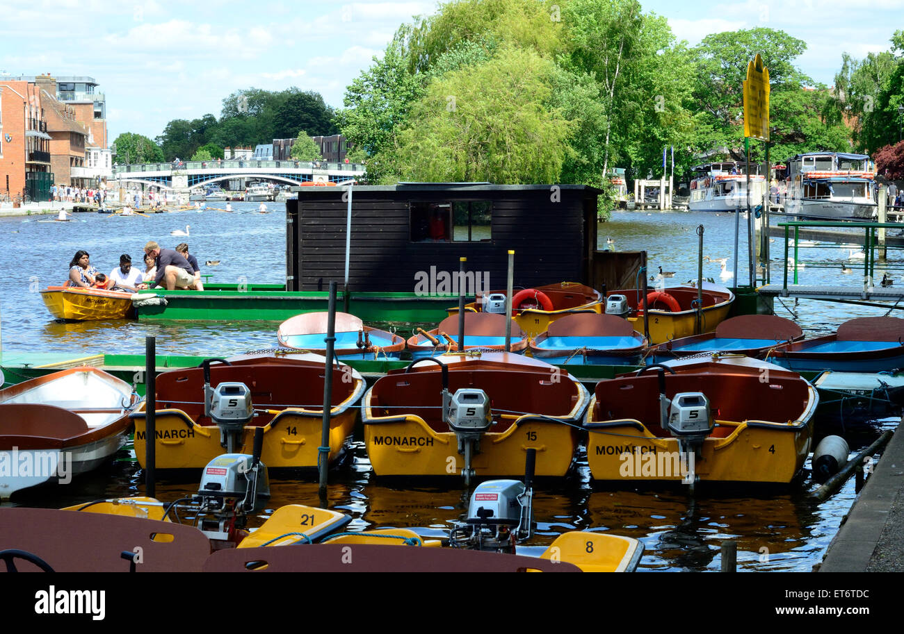 Dinghies with outboard motors line up waiting to be hired by day trippers. - Stock Image