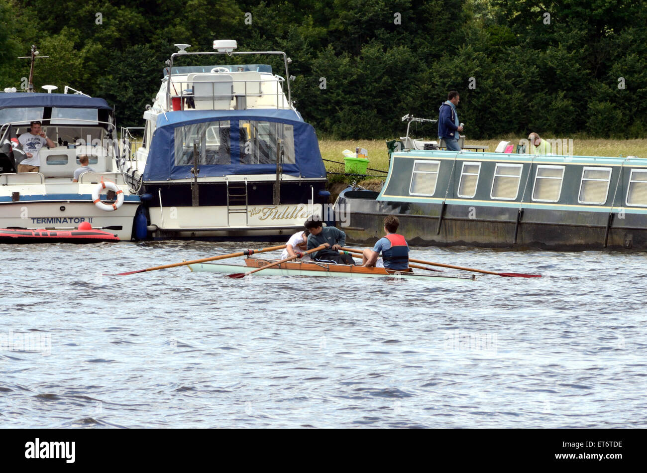 A coxed pair rowing crew row past boats moored on the bank of The River Thames in Windsor. - Stock Image