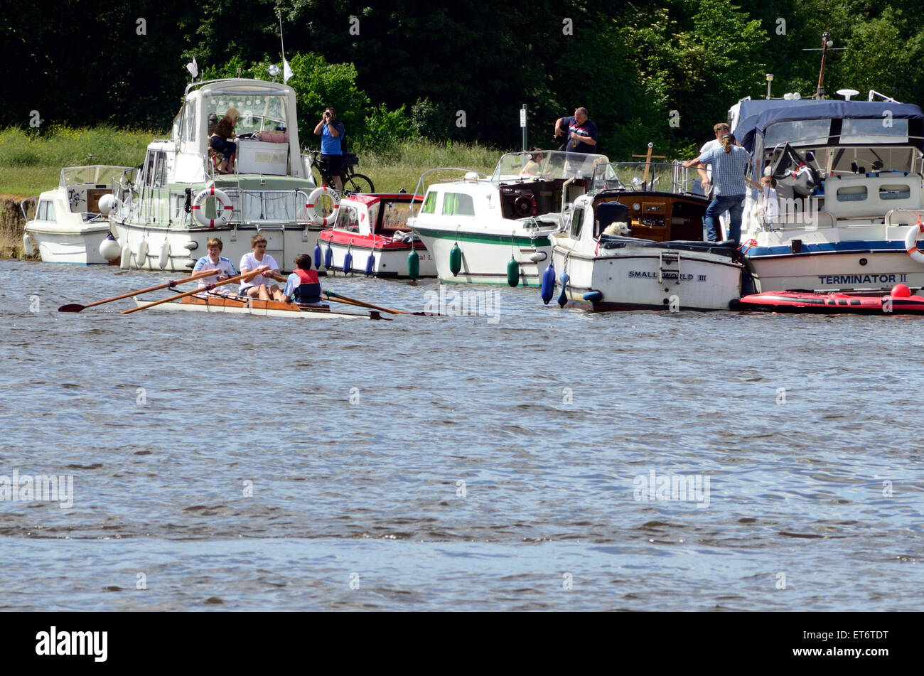 A coxed pair rowing crew row past pleasure boats which are moored on the banks of The River Thames at Windsor. - Stock Image
