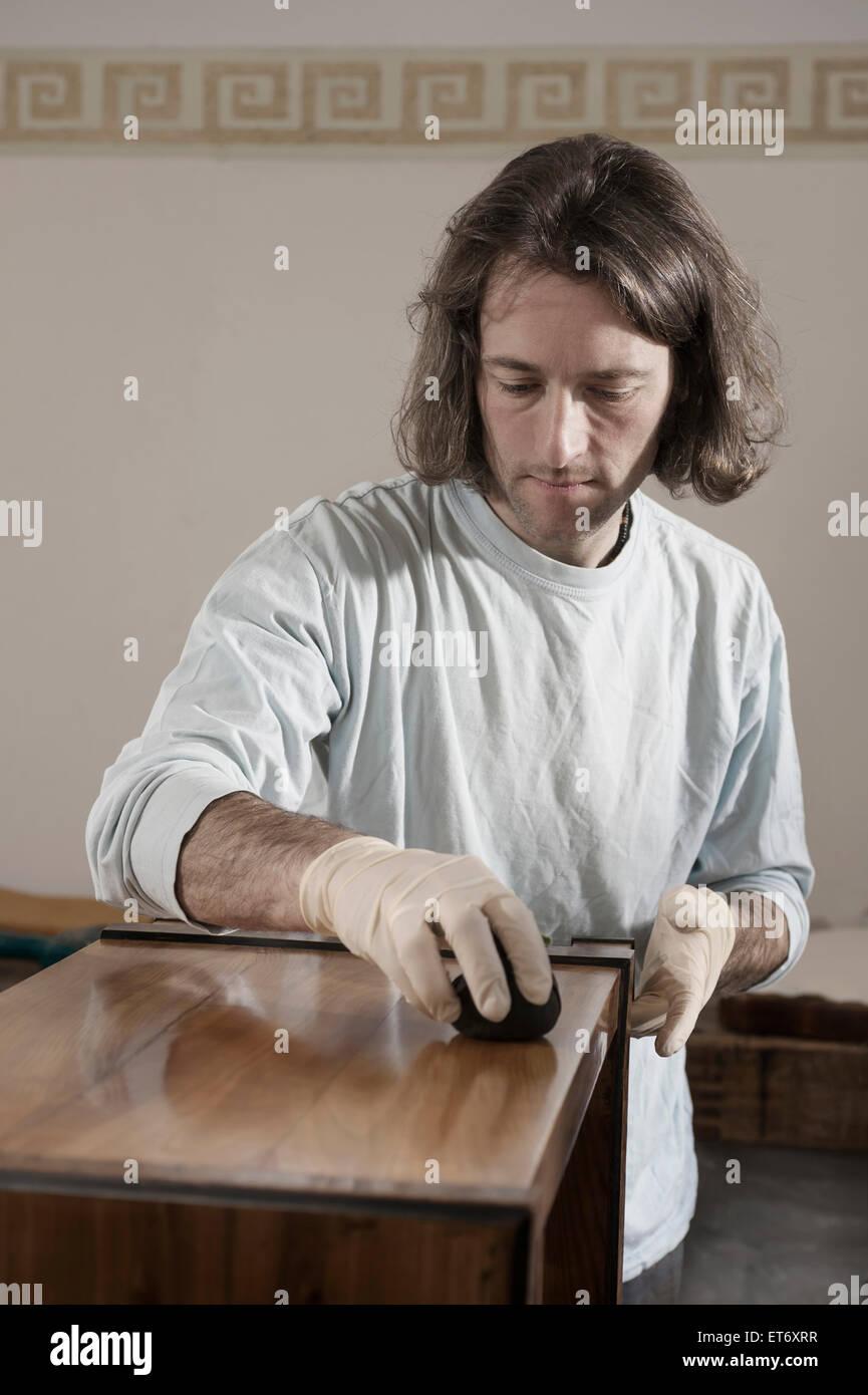Carpenter French polishing on wooden drawer at workshop, Bavaria, Germany Stock Photo